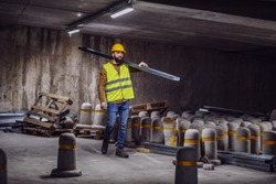 Full length of handsome caucasian bearded worker in vest and helmet on head carrying metal rod on shoulder. Tunnel in construction process interior.