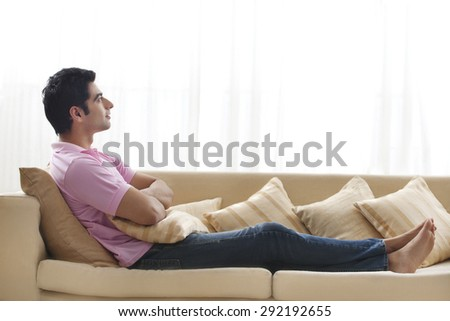 Full length of handsome young man day dreaming on sofa