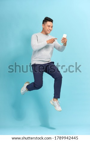 Full length of handsome  young man taking phone while jumping against blue background.