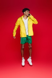 full length of happy african american man in yellow jacket jumping and talking on smartphone on red