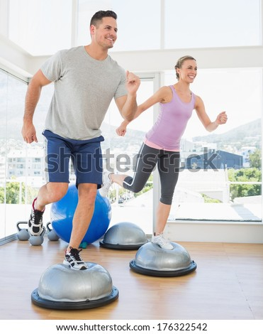 Full length of happy couple doing step aerobics in fitness studio