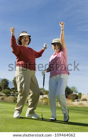 Full length of happy senior women cheering at golf course