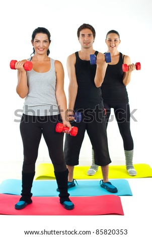 Full length of happy team of people doing fitness and working with dumbbell on colorful mats