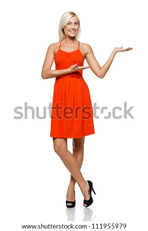 Full length of happy young woman showing a product - empty copy space on the open hand palm, over white background