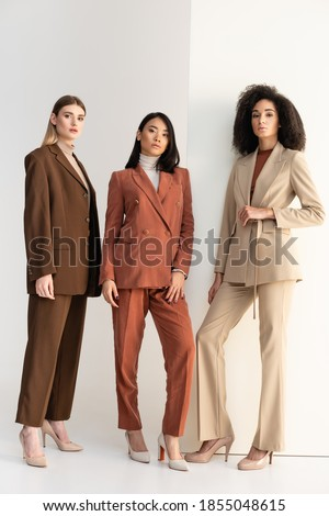 full length of interracial women in formal wear posing on white ストックフォト ©