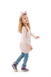 Full length of joyful little girl, dancing.  Isolated on white background