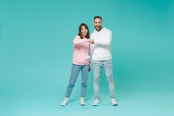 Full length of laughing funny young couple friends man woman in white pink casual hoodie holding hands folded giving fists bump looking camera isolated on blue turquoise background studio portrait