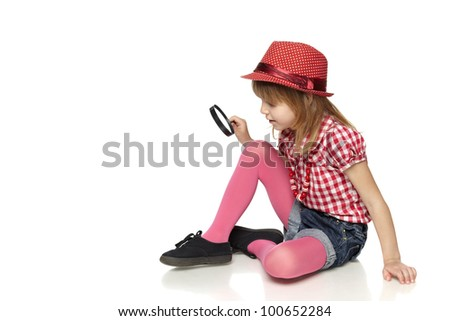 Full length of little girl sitting on the floor with magnifying glass, isolated on a white background
