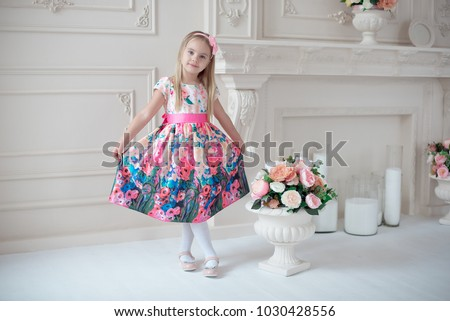 Full-length of little smiling girl child in colorful dress posing indoor. Stock foto ©