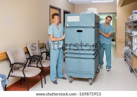 Full length of male and female nurses pushing trolley in hospital hallway