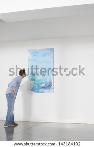 Full length of man observing painting in art gallery