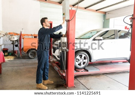 Full length of mid adult car mechanic operating hydraulic lift in repair shop #1141225691