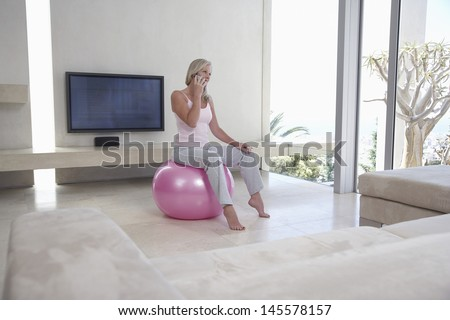 Full length of middle aged woman sitting on fitness ball while using cell phone in living room
