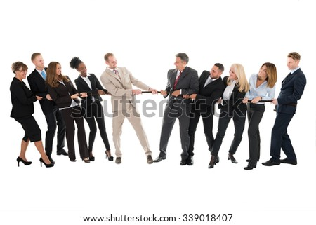 Full length of multi ethnic business teams playing tug of war against white background