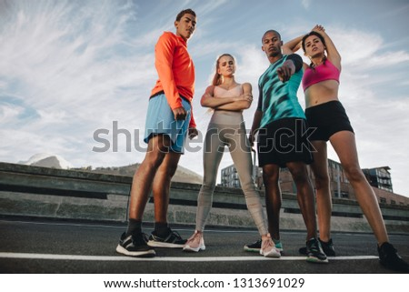 Full length of multi-ethnic group of people standing outdoors on the city street after workout. Fitness group standing together after workout and looking at camera. Low angle shot.