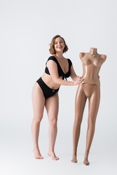 full length of overweight and barefoot young woman laughing near plastic mannequin on white