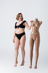 full length of overweight and barefoot young woman smiling near plastic mannequin on white