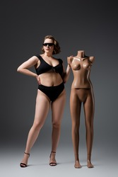 full length of overweight young woman in swimsuit and sunglasses posing with plastic mannequin on grey
