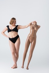 full length of overweight young woman posing with plastic mannequin on white
