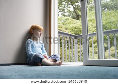 Full length of pensive young girl looking through balcony while sitting on carpet at home