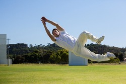 Full length of player diving to catch ball against blue sky over field