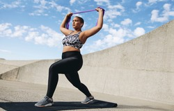 Full length of plus size woman exercising with resistance band. Female doing resistance band workout outdoors in morning.