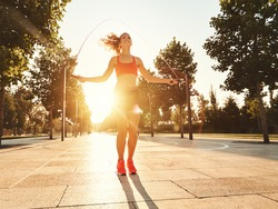 Full length of positive energetic slim female in sportive outfit jumping with skipping rope in sunny summer park