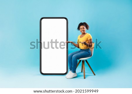 Full length of pretty Afro lady sitting on chair next to big blank smartphone with mockup for mobile app or website design, blue studio background. Space for your online advertisement