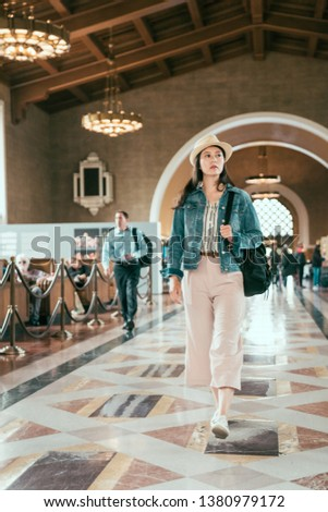 full length of pretty young local woman walking in historical union station Los Angeles. asian female backpacker travel by train. college girl travel in usa commute in summer break holidays.