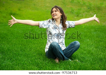 Full length of pretty young woman. Full length of pretty young woman resting on grass and smiling. Greeting with opened arms resting on grass and smiling. Greeting with opened arms