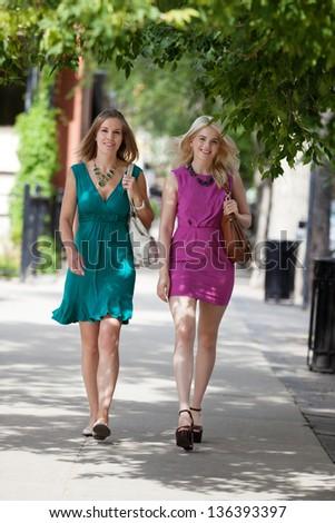 Full length of pretty young women walking on sidewalk