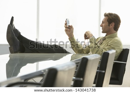 Full length of relaxed businessman with feet up text messaging on cell phone in conference room