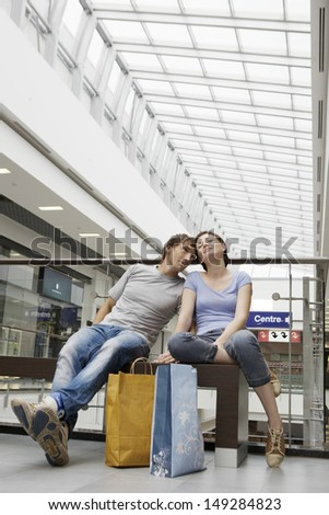 Full length of romantic young couple with shopping bags in mall #149284823