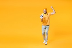 Full length of shocked amazed young man wearing basic casual t-shirt headphones hat screaming in megaphone clenching fist looking camera isolated on bright yellow colour background, studio portrait
