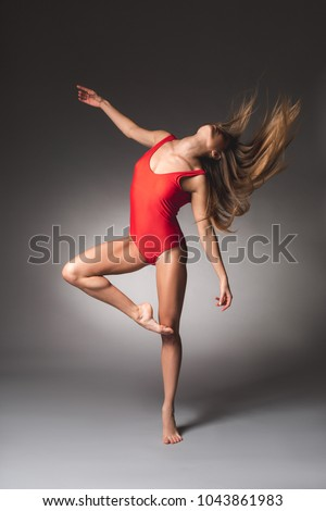 Full length of slim woman dancing in tight red swimsuit. Her hair are disbanded
