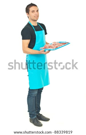 Full length of smiling butcher in blue apron holding meat isolated on white background