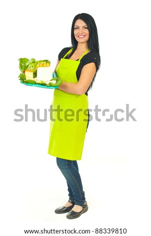 Full length of smiling cheese maker woman with green apron holding different cheese on plateau in a supermarket isolated on white background