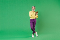 Full length of smiling elderly gray-haired mustache bearded man in basic yellow shirt suspenders using mobile cell phone typing sms message isolated on bright green colour background, studio portrait