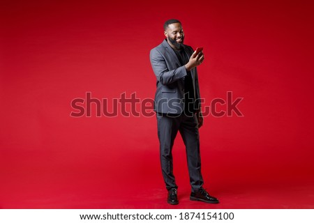 Full length of smiling successful young african american business man 20s in classic jacket suit using mobile cell phone typing sms message isolated on bright red color background studio portrait