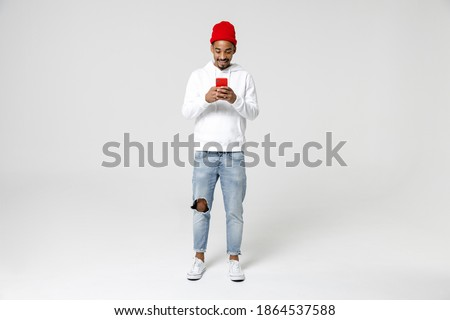 Full length of smiling young african american man 20s years old in casual streetwear hoodie standing using mobile cell phone typing sms message isolated on white colour background, studio portrait