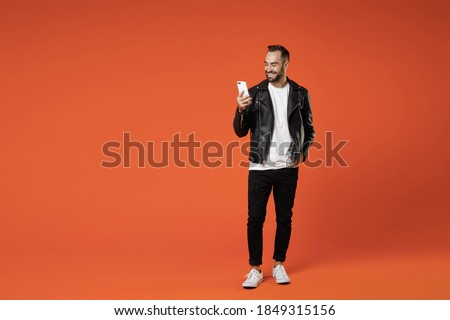 Full length of smiling young bearded man 20s wearing basic white t-shirt black leather jacket standing using mobile cell phone typing sms message isolated on orange colour background studio portrait