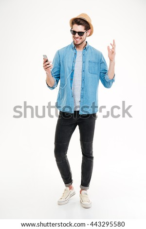 Full length of smiling young man listening to music from smartphone over white background stock photo