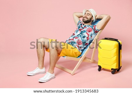 Full length of smiling young traveler tourist man in summer clothes hat sit on deck chair hold hands behind head isolated on pink background. Passenger travel on weekend. Air flight journey concept