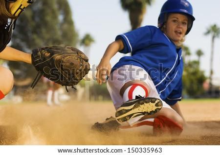 Full length of softball player sliding into home plate