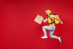 Full length of step delivery employee man in yellow cap t-shirt thermal backpack hold craft paper food takeaway bag work courier service during quarantine covid19 jumping isolated on red background