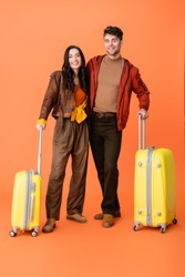 full length of stylish couple in autumn outfit standing near yellow baggage on orange
