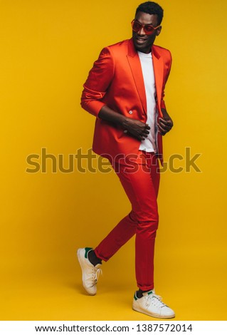 Full length of stylish young african man in orange outfit over yellow background. Fashion model in smart casuals.