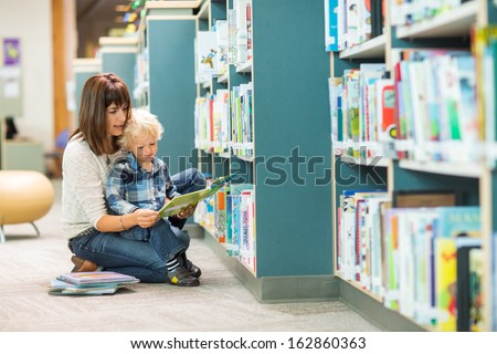 Full length of teacher and boy reading book by bookshelf in library