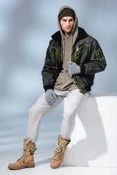 full length of trendy man in hat, gloves and parka sitting on white cube on grey