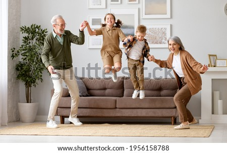 Full length of two excited kids siblings having fun playing with active and positive grandparents in the living room at home, enjoying weekend time with energetic senior old grandma and grandpa Stockfoto ©